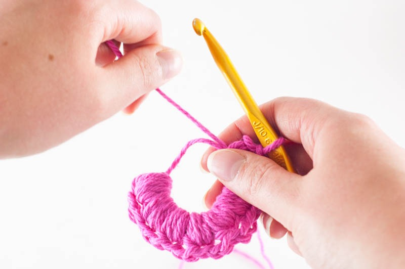 two hands pulling pink yarn to close the magic ring