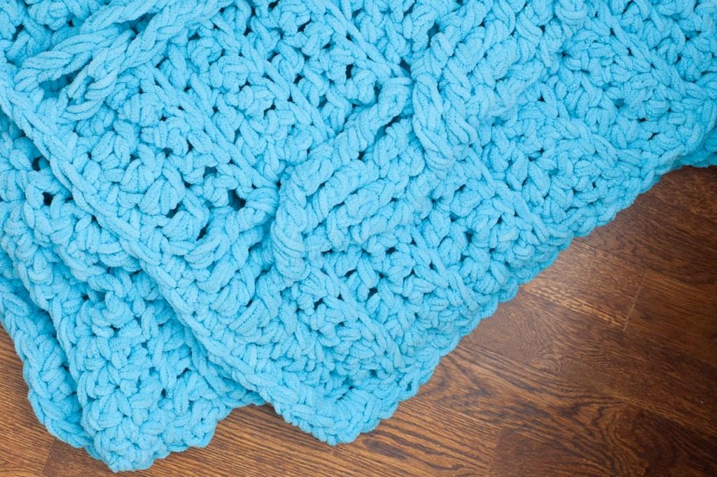 Chunky blue crochet blanket on a hardwood floor