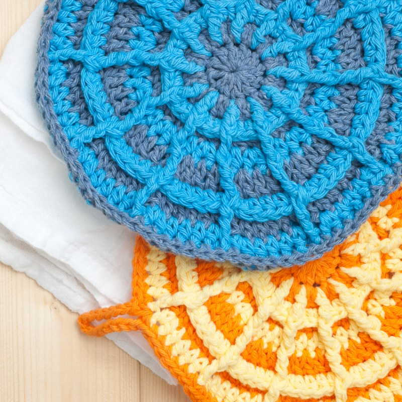 Two crochet potholders (orange and blue) and a white towel on a light wood background.