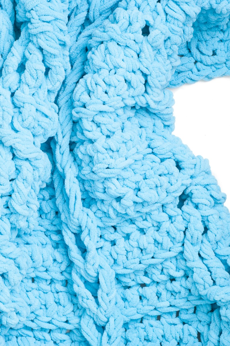 Vertical image of a blue chunky crochet throw blanket with cables and braided chains.