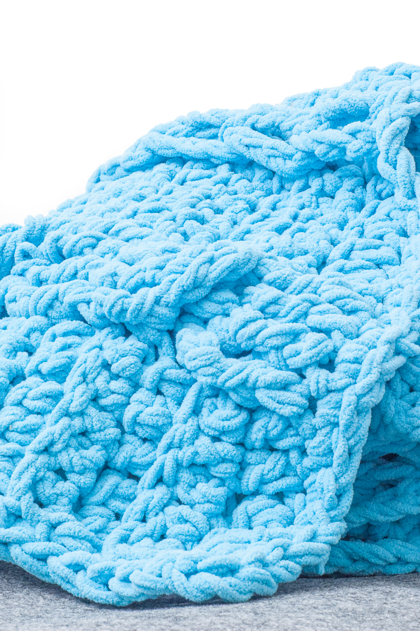 Side view of a blue crocheted blanket with cables and braided chains.