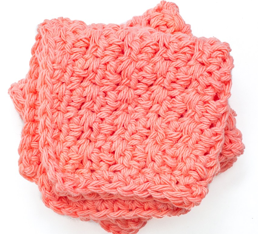 two coral-colored crochet washcloths folded into squares