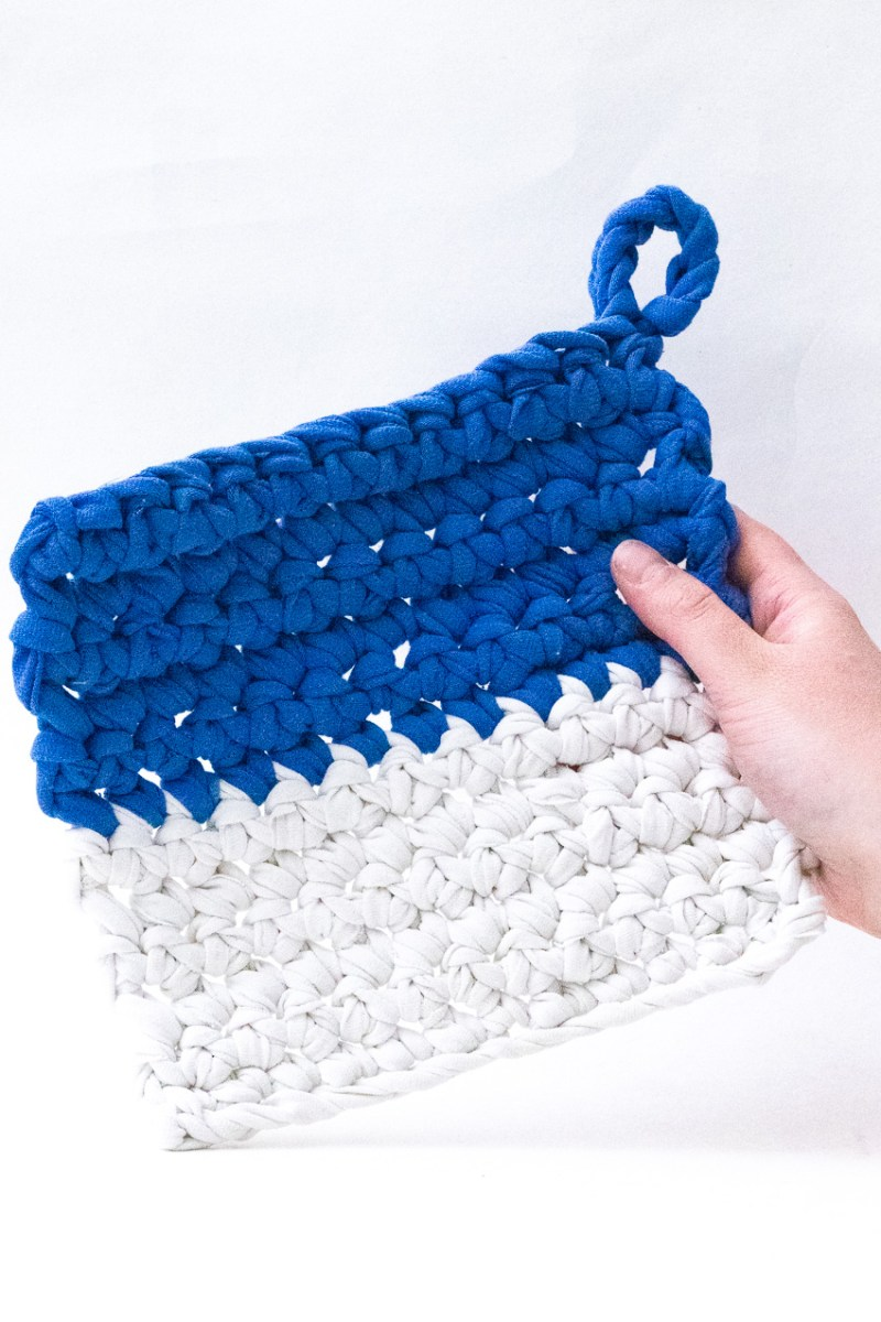 hand holding a blue and white crocheted potholder against a white background