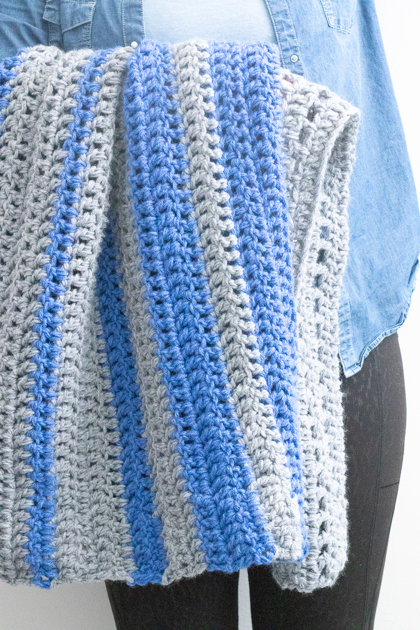 woman standing and holding a blue and grey crocheted blanket over her arm