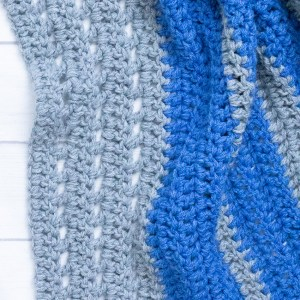 close-up of a grey and blue crocheted blanket on a white background