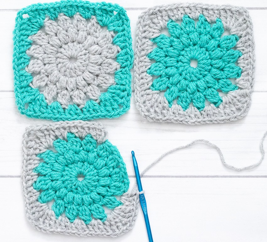three sunburst granny squares and a crochet hook on a white background