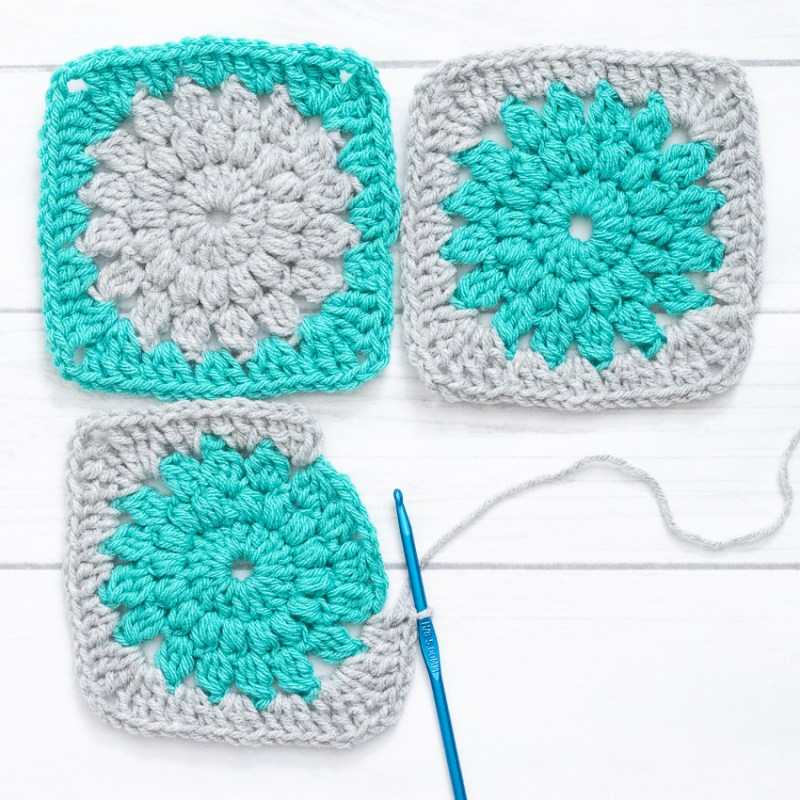 three sunburst granny squares and a blue crochet hook on a white background