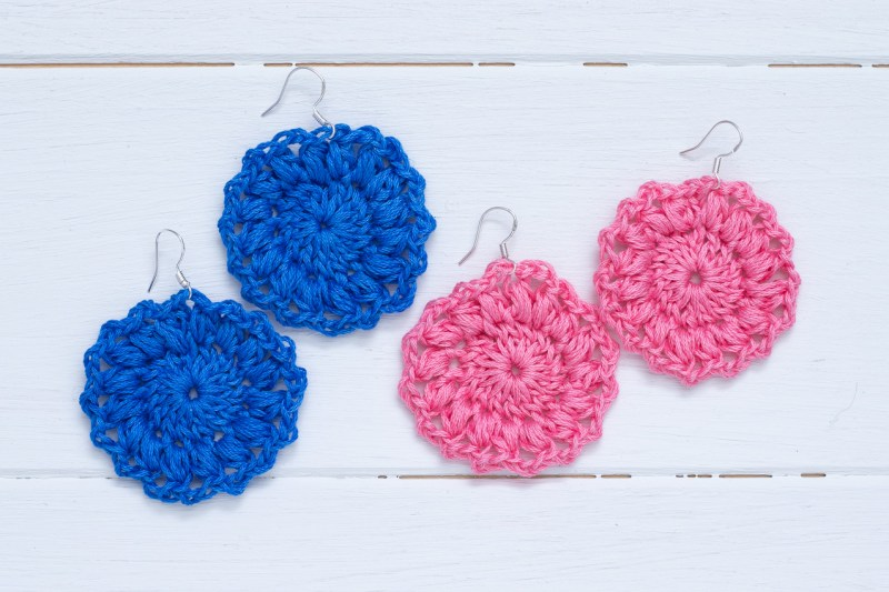 two sets of crocheted sunburst earrings on a white wood background