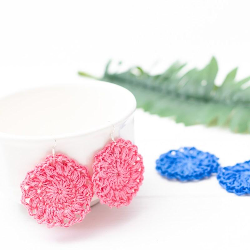 pink crocheted sunburst earrings hanging on a white mug