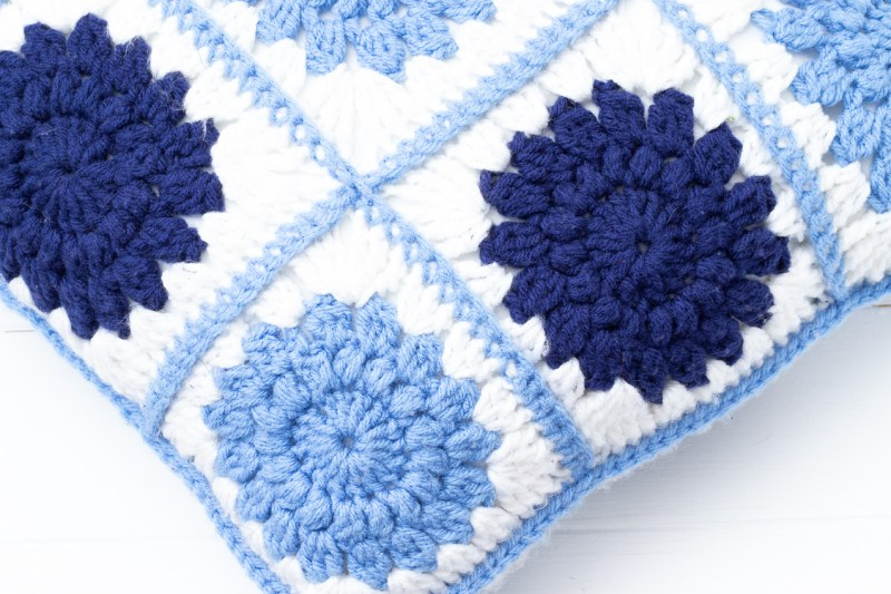 crocheted sunburst pillow in navy, light blue, and white
