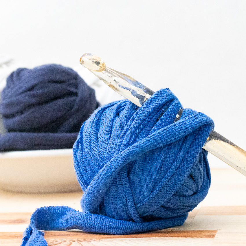 Blue ball of t-shirt yarn with a crochet hook