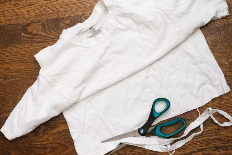 white t-shirt with the bottom seam being cut off by black and green scissors