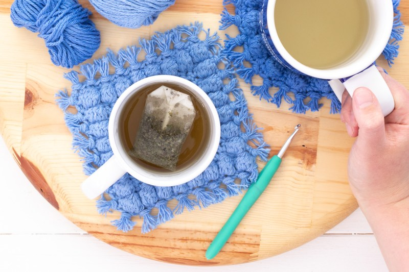 round wooden cutting board with crocheted bobble coasters and mugs with tea
