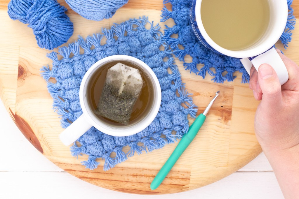 round wooden cutting board with mugs of tea, a crochet hook, and boho bobble coasters