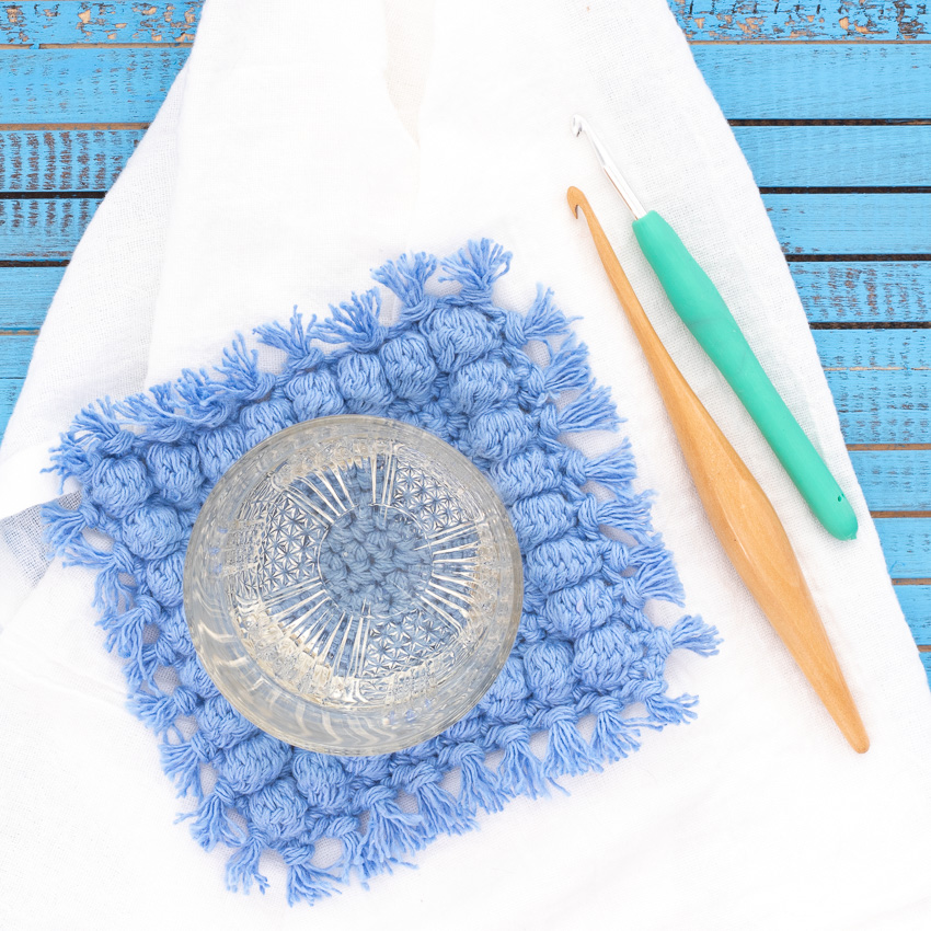 white towel on a blue wood background, with a square bobble coaster and two crochet hooks