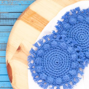 round wooden cutting board with two round crocheted bobble coasters