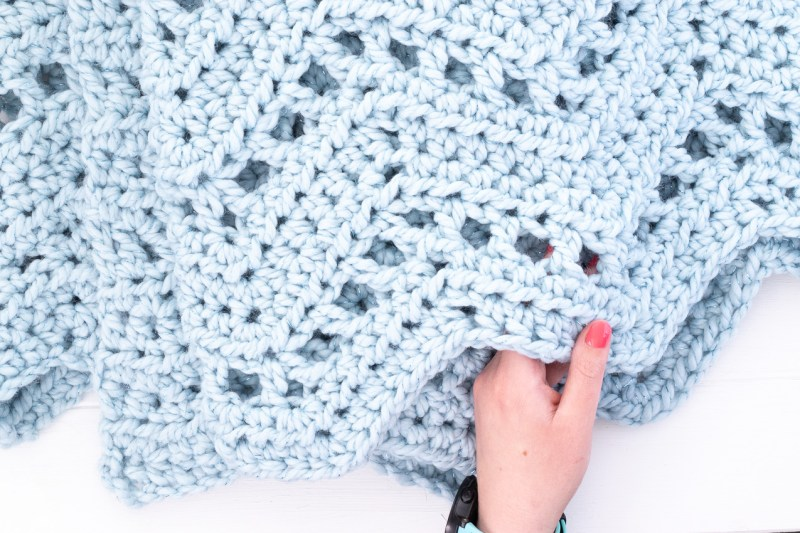 hand holding a blue chunky crocheted ripple blanket