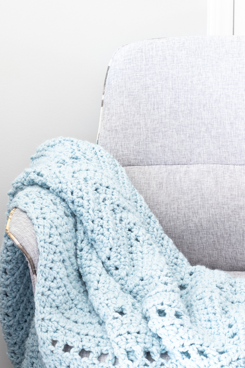 grey chair with a blue crochet ripple blanket over the arm