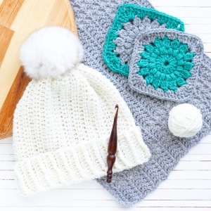 white twisted whims hat with a wooden crochet hook and other crocheted items