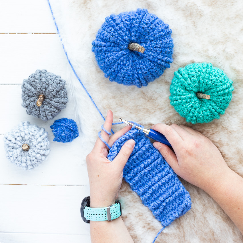 two hands crocheting a blue strip with pumpkins and fur in the background