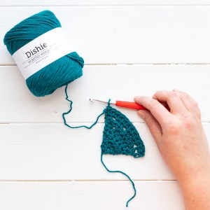 hand holding a red crochet hook and a triangular swatch attached to a small ball of teal Dishie yarn
