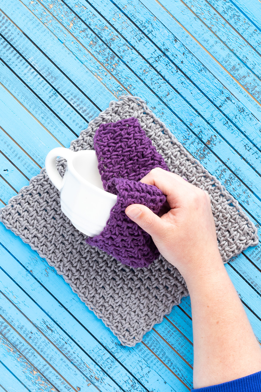 hand holding a white mug with a purple linen stitch dishcloth on a grey dishcloth on a blue wooden background