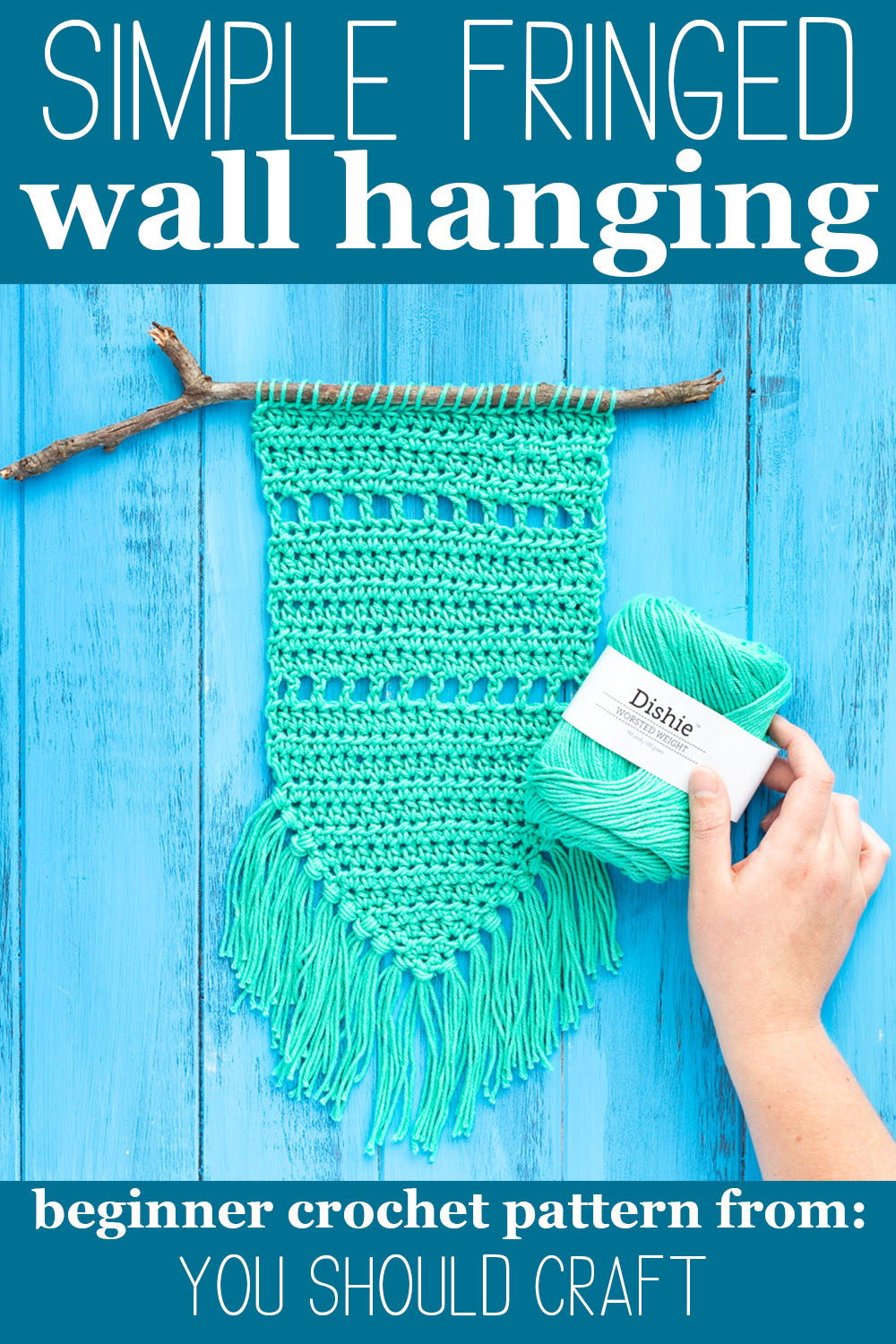 """crocheted wall hanging and a hand holding dishie cotton yarn with text """"simple fringed wall hanging - beginner crochet pattern from: you should craft"""""""