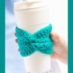 hand holding up a cup with a teal crocheted coffee sleeve