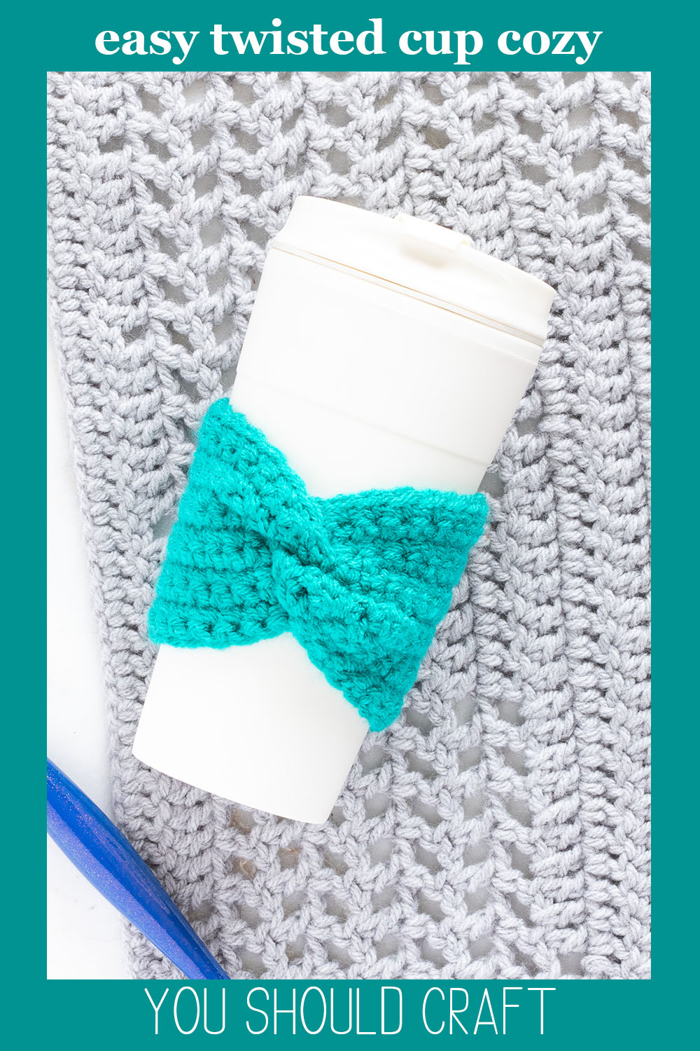 cream-colored coffee cup with a teal crochet cup cozy on a grey background