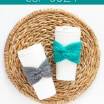 two coffee cups with crocheted cup cozies on a woven placemat