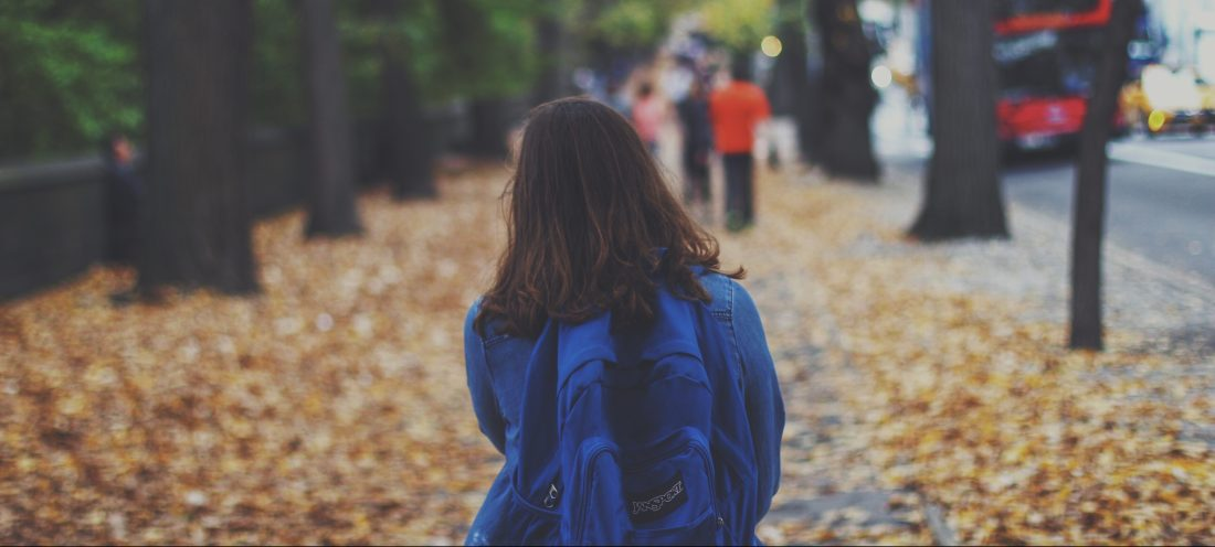 Girl wearing backpack facing away walking down a street in autumn