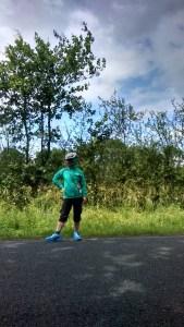 Julia in her biking gear, posing beside the open road.