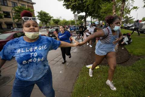 Protesters run from percussion grenades and teargas Photograph: Carlos Gonzalez/AP