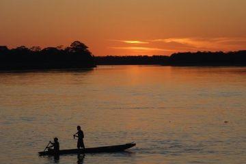 Voyage au Perou: Le soleil se couche sur l'Amazonie, les quelques pêcheurs encore sur l'eau rentrent.