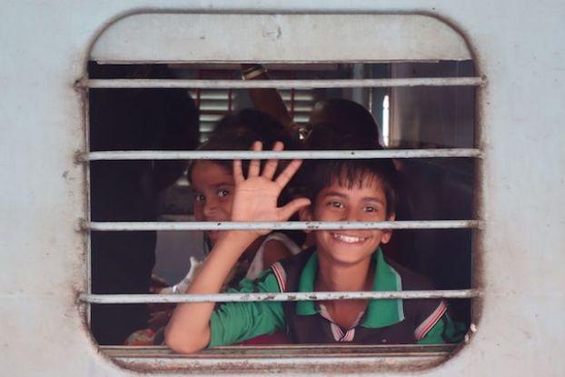 Wagon avec un enfant entrain de sourir dans la gare de jaipur photo blog voyage tour du monde http://yoytourdumonde.fr
