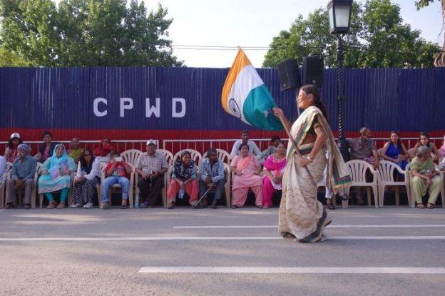 Une femme indienne avec un drapeau indien le long de la frontiere pakistanaise à Amristar en Inde photo blog voyage tour du monde http://yoytourdumonde.fr