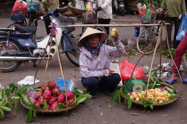 Hanoi-Vietnam: Vendeuse ambulante avec chapeau conique.