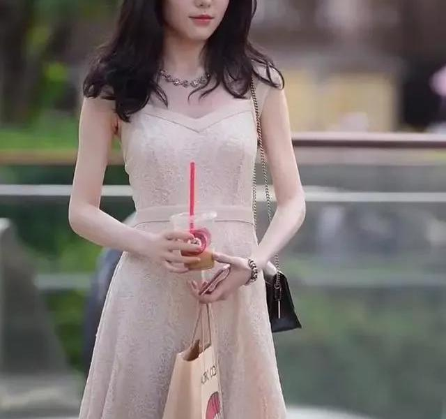 Street shot:immortal young woman, wearing a light coffee-colored hollow dress, it is difficult to conceal her beautiful posture