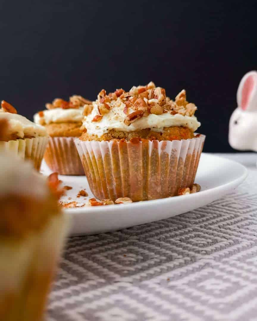 Low carb carrot cake cupcakes, frosted on a plate with the Easter bunny sneaking into frame