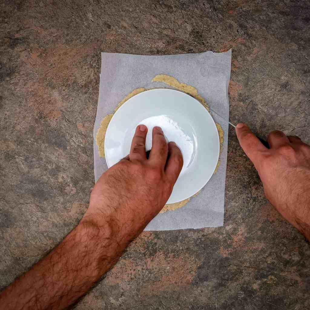 Keto Tortilla dough being cut to shape