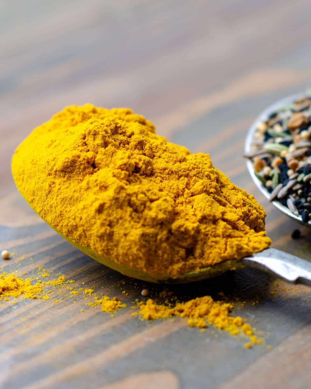 Food photography of ground Turmeric on a spoon with spices in the background
