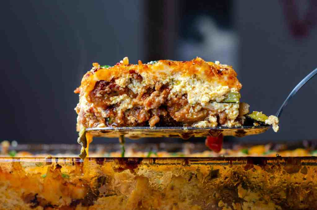 Ultimate Keto Zucchini Lasagna on a spatula over a pan