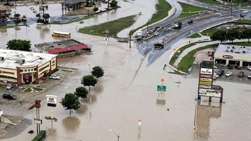 A shopping center located at Texas 80 near I-35 has high water in the parking lots from the Blanco River flooding in San Marcos,Texas, on Sunday, May 24, 2015. (Rodolfo Gonzalez/Austin American-Statesman via AP) AUSTIN CHRONICLE OUT, COMMUNITY IMPACT OUT, INTERNET AND TV MUST CREDIT PHOTOGRAPHER AND STATESMAN.COM, MAGS OUT