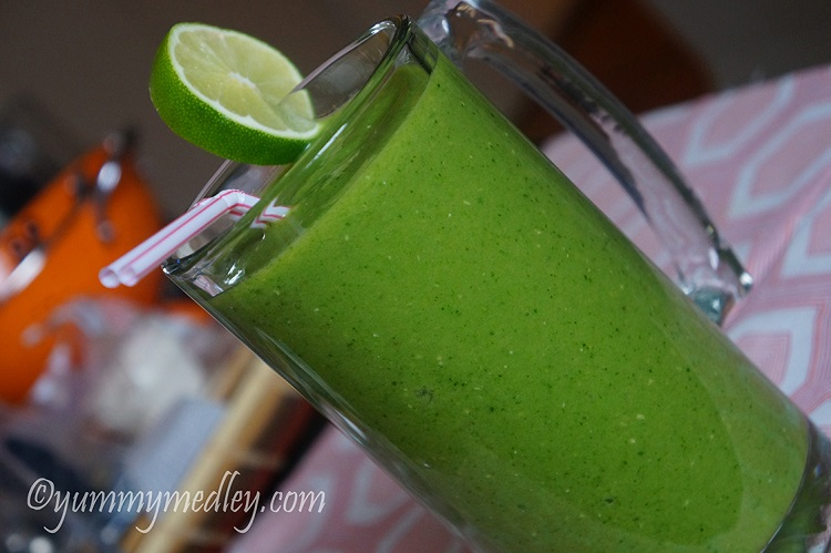 Tropical Island Green Smoothie - A cup of smoothie with lemon slice