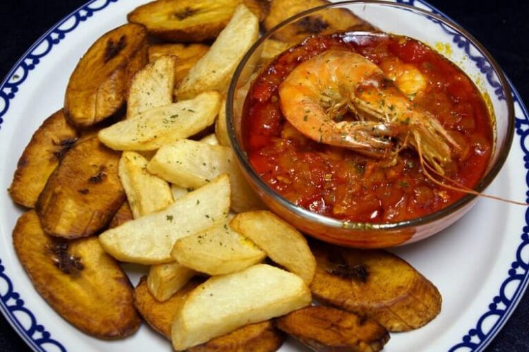 Tomato Sauce with shrimp plated and served with plantains and fries