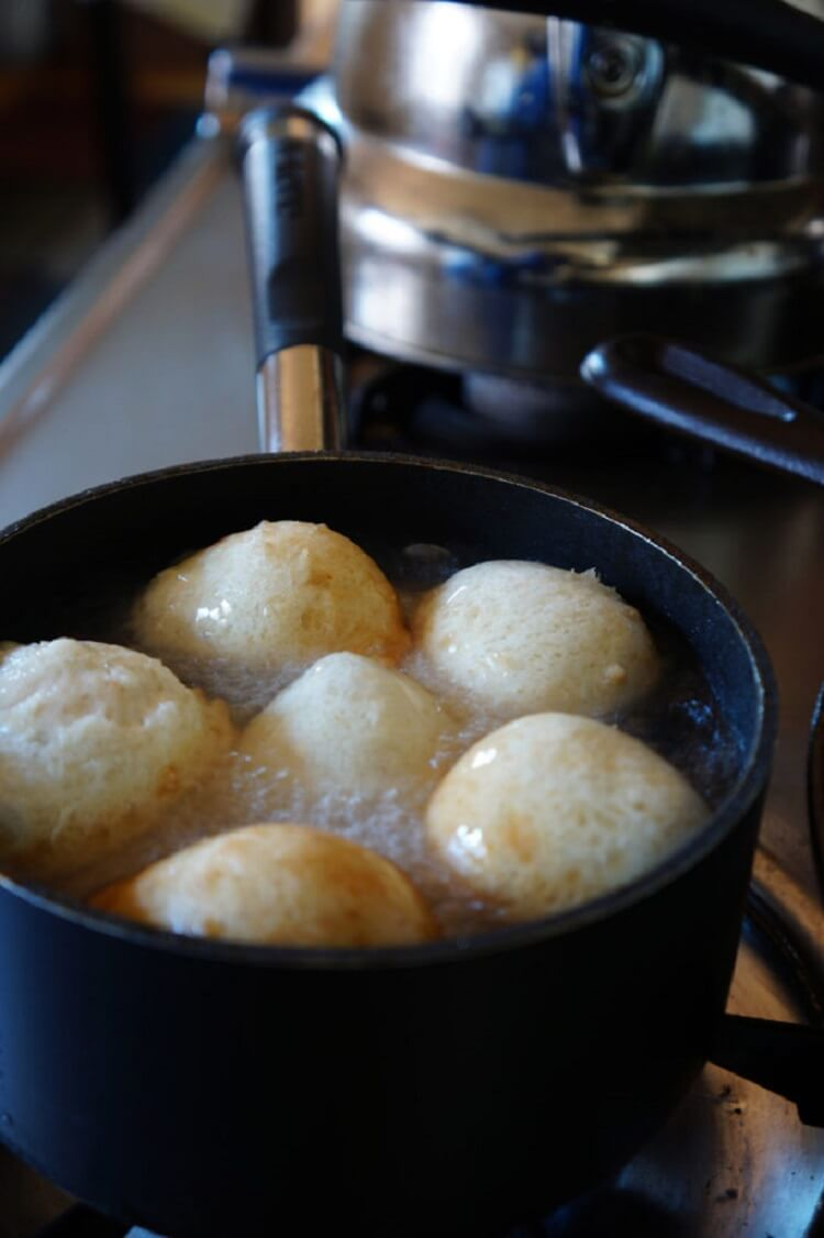 Deep frying the scooped dough balls in a pan