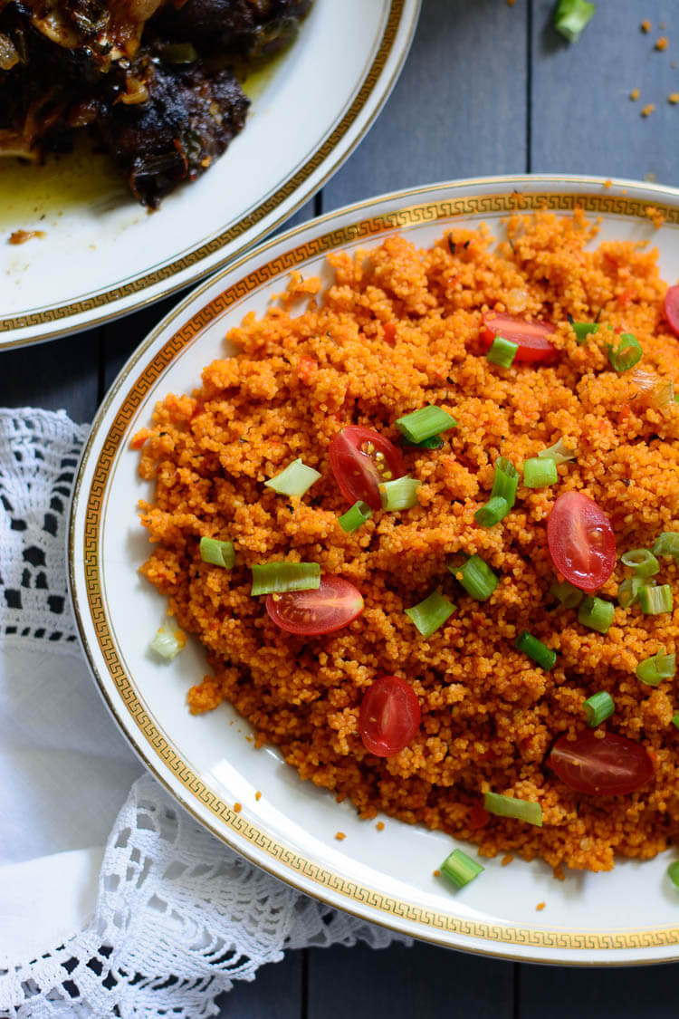 Jollof Couscous in 20 Minutes! - Jollof couscous garnished with grape tomatoes and green onions with a plate of goat meat on the side