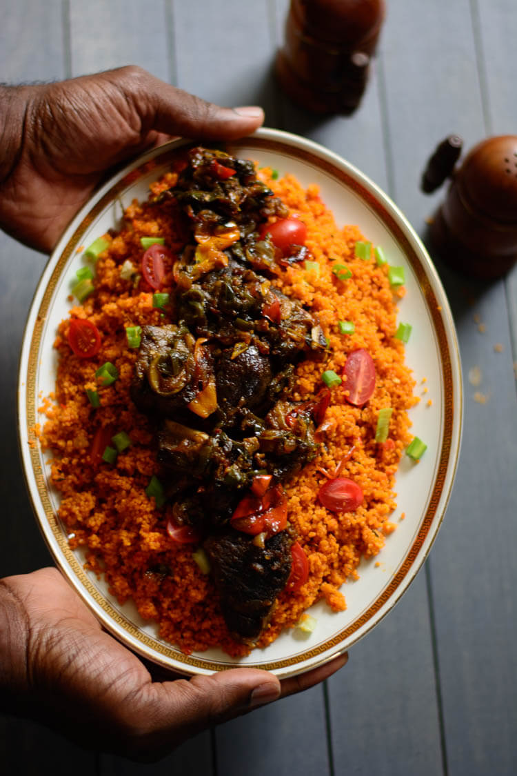 Jollof Couscous in 20 Minutes! - hands presenting Jollof couscous garnished with grape tomatoes, green onions and goat meat