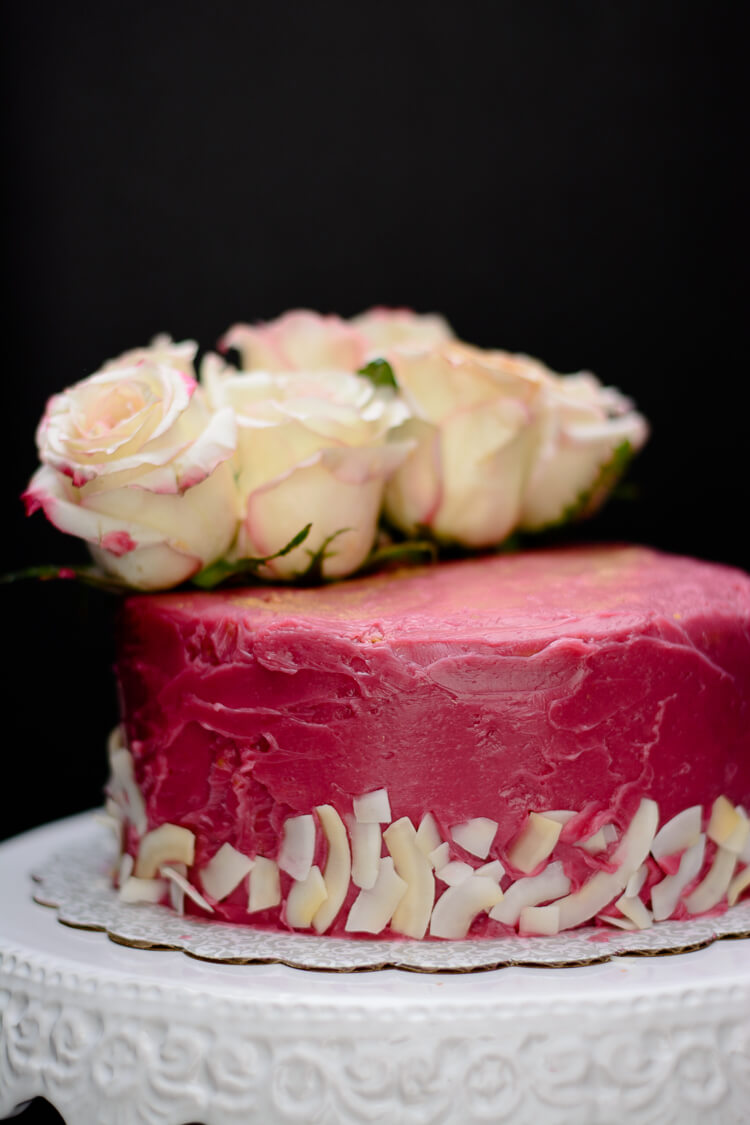 Earl grey tea cake with hibiscus frosting decorated with coconut flakes and roses