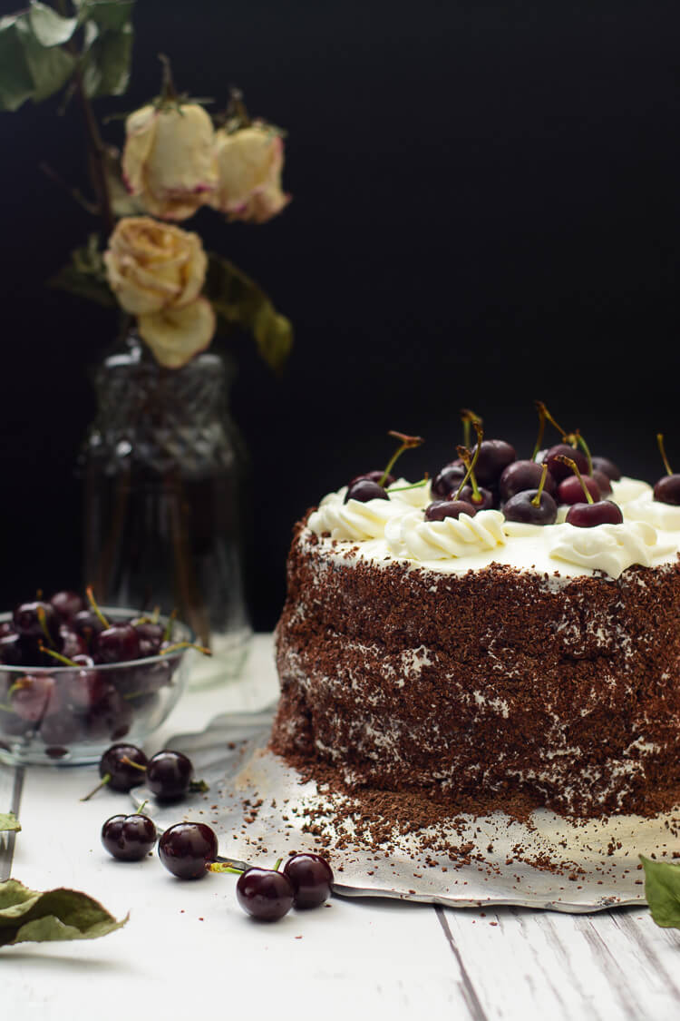 cake on table with cherries littered around